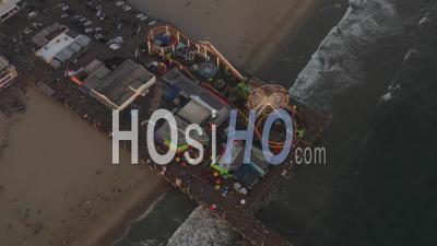 Encerclant La Jetée De Santa Monica, Los Angeles D'en Haut Au Beau Coucher De Soleil Avec Des Touristes, Des Piétons S'amusant Au Parc à Thème Grande Roue Avec Vue Sur L'océan Vagues S'écraser 4k - Vidéo Aérienne Par Drone