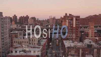 Vue Aérienne à La Suite De Voitures Roulant Sur Le Viaduc Au-Dessus Des Bâtiments Résidentiels Dans Le Quartier Chinois Vers Le Pont De Manhattan 4k - Vidéo Par Drone