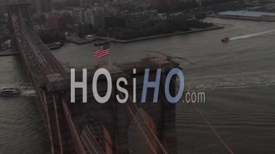 Close Up Circle Flight Over Brooklyn Bridge With American Flag And East River View Manhattan New York City Skyline In Beautiful 4k - Video Drone Footage