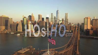 Vol Au-Dessus Du Pont De Brooklyn Avec Le Drapeau Américain Agitant Et Vue Sur La Rivière East Sur Les Toits De Manhattan New York City Dans De Beaux 4k - Drone Vidéo