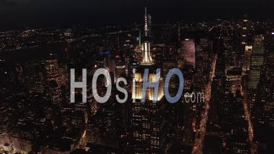 Breathtaking Wide View The Iconic Empire State Building Disappearing Behind Residential Condominiums And Office Buildings In Midtown Manhattan, New York City At Night 4k - Video Drone Footage